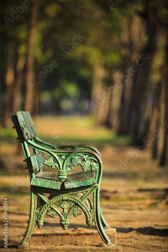 old green bench in park with blurry background