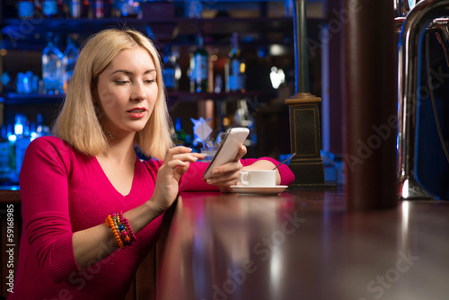 woman with a cup of coffee and cell phone