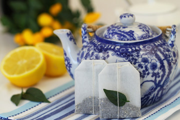 Tea bags, vintage teapot and fresh lemon