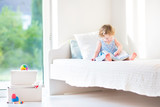 Adorable toddler girl reading a book sitting on a white bed next