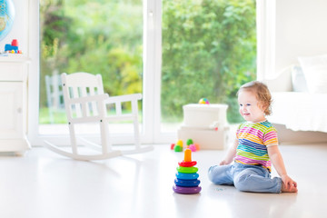 Adorable toddler girl playing with a colorful pyramis in a beaut