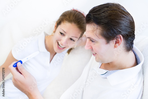 Young happy couple looking at a positive pregnancy test
