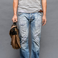 Casual wear man wearing jeans and sleeveless shirt holding bag