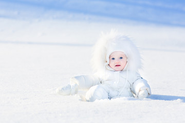 Funny little baby playing in snow on a sunny winter day