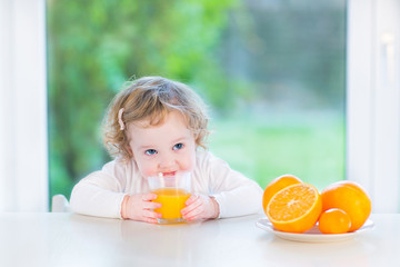 Cute toddler girl drinking orange juice sitting at a white table