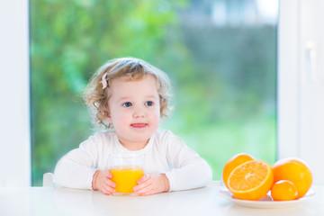 Toddler girl drinking orange jiuce sitting at a white table