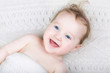 Cute laughing baby under a warm knitted blanket