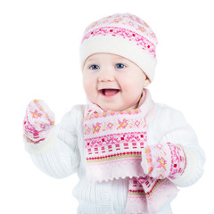 Laughing baby girl wearing warm hat, scarf and mittens