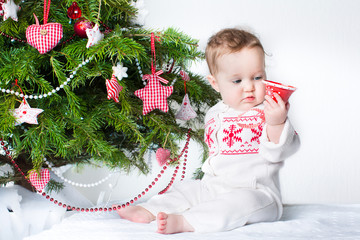 Cute baby girl playing with a toy bell under a Christmas tree