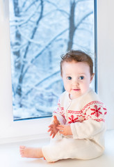 Beautiful baby girl sitting next to a window to a snowy garden