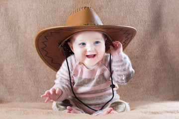 Happy laughing baby wearing a cow girl outfit with a big hat
