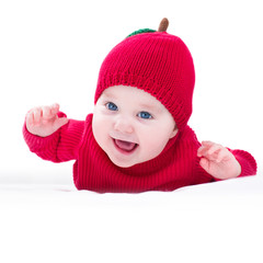Funny laughing baby wearing a knitted red apple hat