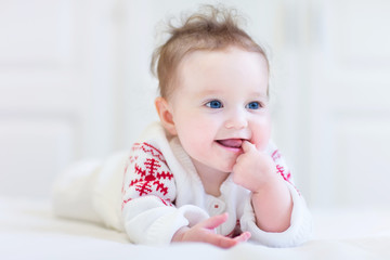 Baby wearing a knitted sweater with red Christmas snowflake