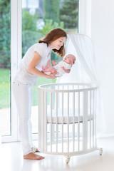 Mother putting her newborn baby to sleep in a white round crib