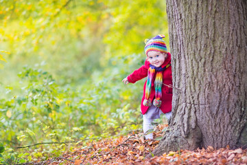 Sweet funny baby girl in a red coat and colorful hat in a park