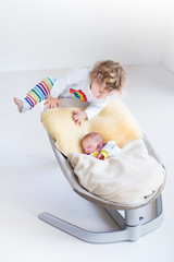 Toddler girl climbing on a swing with her newborn baby brother