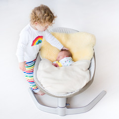 Newborn baby sleeping in a swing on a sheepskin with his sister