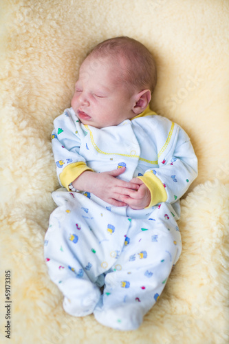 Newborn baby boy sleeping on a sheepskin