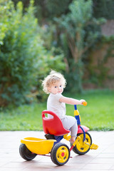Cute baby girl riding her first bicycle in the park