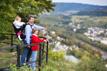 Young active father hiking in a beautiful autumn cliff and fores