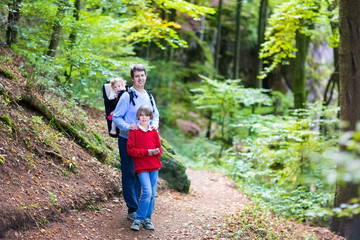 Active father hiking in a beautiful autumn cliff and forest