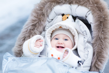 Happy laughing baby girl enjoying a walk in a snowy winter parl