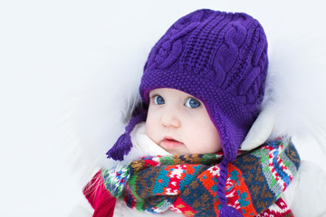 Cute baby girl wearing a warm winter hat and a colorful scarf