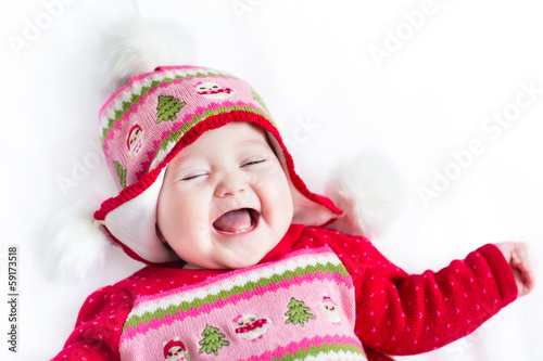 Portrait laughing baby on a white blanket wearing christmas hat