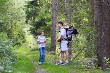 Young father hiking with his school age son and baby daughter