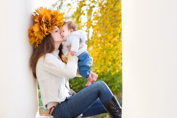 Young mother with maple leaves wreath sitting between