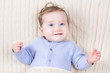 Close up portrait of an baby in a warm blue knitted sweater
