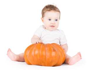 Cute baby girl playing with a big pumpkin on white background