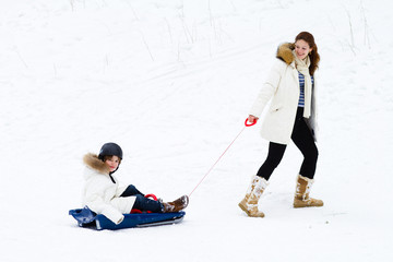 Young beautiful mother and her school age son enjoying a sleigh