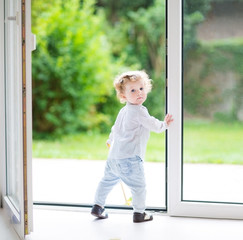Curly baby girl standing at a big glass door to the garden