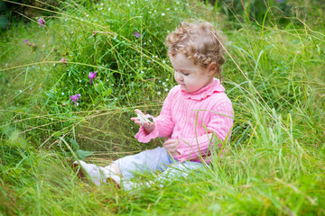 Cute baby girl playing with a snail in the garden among flowers
