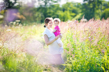 Pregnant mother and her toddler walking in a sunny meadow