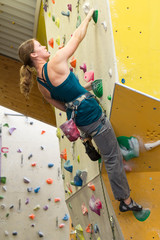 young healthy woman climbing rock wall indoors
