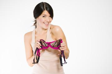 Junge flirtende Frau hält einen BH aus zarter Spitze