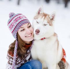 teen girl embracing cute dog in winter park
