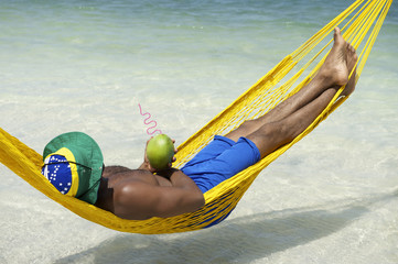 Man Relaxing in Hammock Brazilian Beach with Coconut