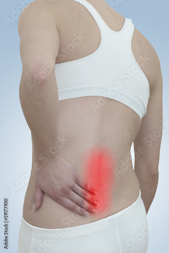 Acute pain in a woman back. Female from behind holding hand to s