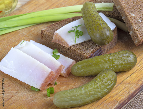 Pickled cucumber,pieces of lard and pieces of black bread