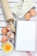 Notebook , eggs, flour and rolling pin