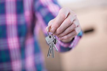 Frau zeigt Schlüssel für Wohnung