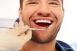 Happy man doing teeth checkup at dentist's surgery