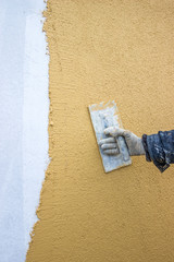 trowel with glove hand plastering a wall