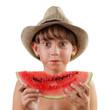 Cute girl in hat eats ripe watermelon