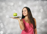 Young girl holds book and apple at light background