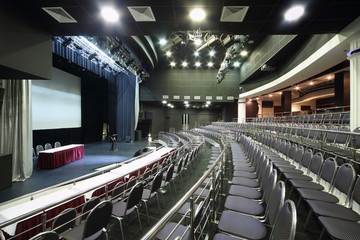 Rows of black chairs and stage in big black hall