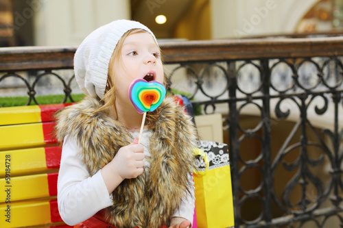 Little beautiful girl licks multicolored lollipop and sits